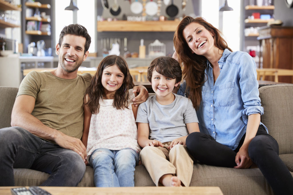 two parents and two children sit on couch for photo